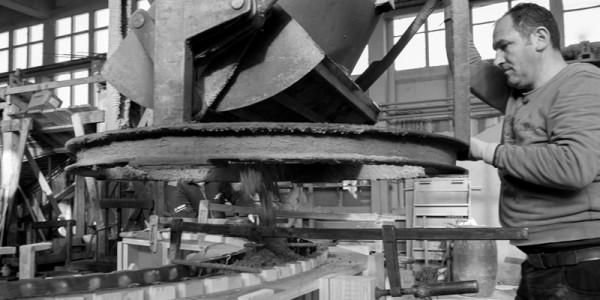 Mann mit Betonkübel in Produktionshalle