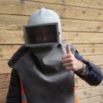 Neues ausprobieren - enthusiastisches Probetragen der Sandstrahl-Schutzmaske auf dem Werksrundgang