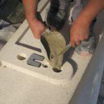 Ein Mitarbeiter füllt Mörtel in einen Verbindungspunkt zweier vorfabrizierter Betonelemente.