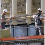 Mitarbeiter setzen das vorfabrizierte Element. Ein Element besteht aus fünf Teilen. Das Setzen der Einheit auf der Baustelle erfordert Geduld und exakte Arbeitsweise.