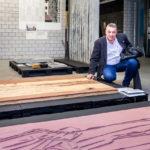 Stefan Stüssi neben einer gefrästen Holzplatte des Mammutbaums. Im Vordergrund die Kunststoffmatrize.